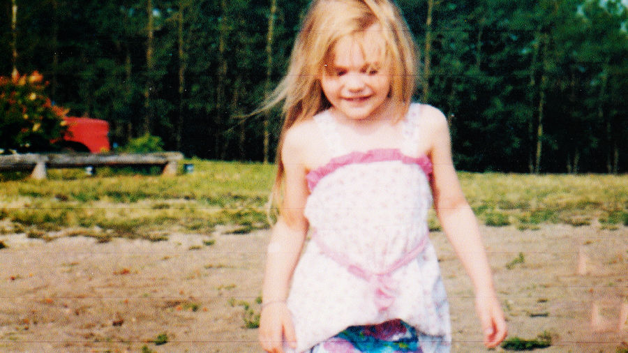 Cover Photo: Photograph of a young child with long blonde hair, wearing a frilled tanktop and smiling as she looks down at the ground. Behind her is a grove of trees.