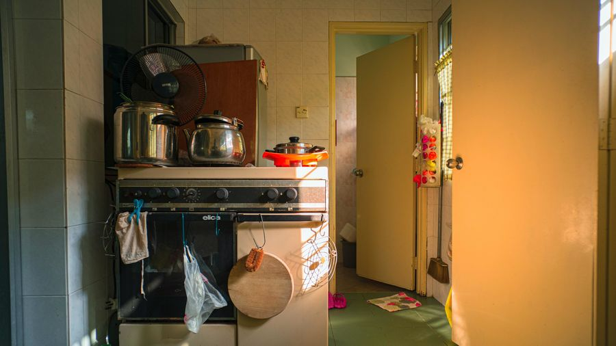 Cover Photo: In this photograph, we are looking into a small kitchen: pushed up against a fridge, we see an old oven, whose stovetop balances a shiny pot and kettle. There are towels and rags and old plastic bags hung from the oven's handles and scattered across the floor. A butter-yellow door opens on the right of the photo, mirroring a yellow door opening to a different room behind the kitchen. The light coming in through the windows is also butter-yellow.