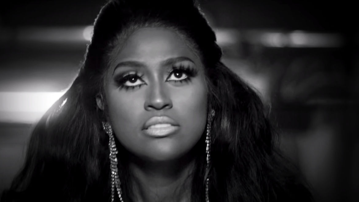 Cover Photo: A black-and-white screencap of singer Jazmine Sullivan facing the camera but looking above it, mouth gritted, with silver dangling earrings, thick, false eyelashes, and a voluminous hairstyle.