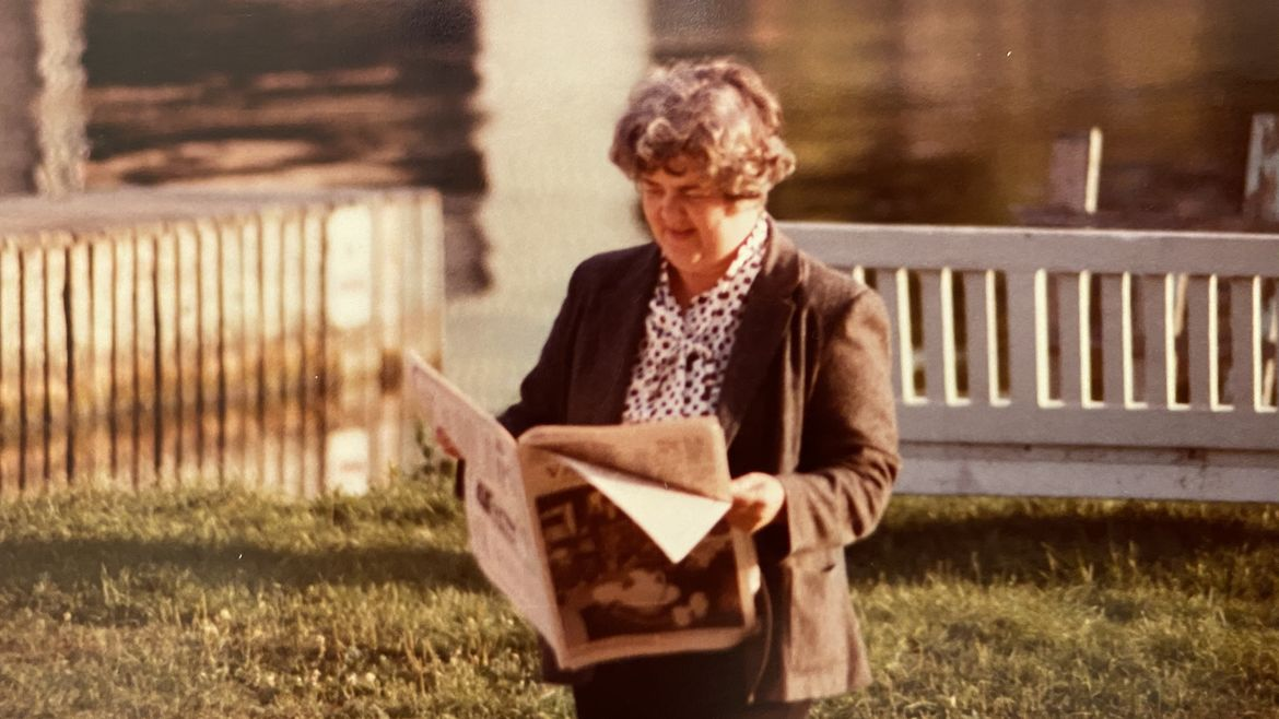 Cover Photo: This photograph of the author's grandmother shows her standing in the grass in front of a lake, holding a newspaper and reading it with a smile on her face. The light is yellowy, like it often is in old color photographs