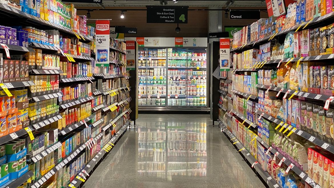 Cover Photo: A photograph of a brightly-lit grocery store aisle. The shelves on the left and right are stocked with canned and boxed goods, and at the end of the aisle is a large fridge filled with bottles and tubs.