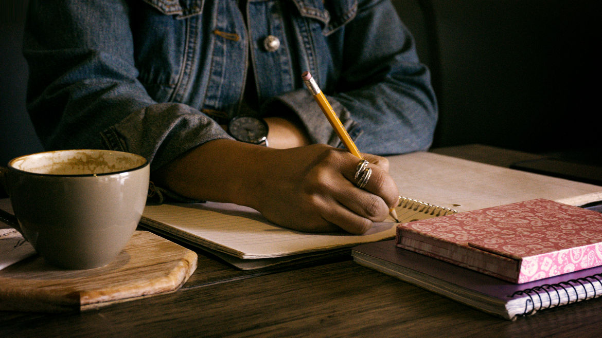 Cover Photo: photograph of a person in a denim jacket sitting at a wooden table, writing in a spiral notebook with a pencil, a stack of books and a cup of coffee on the table