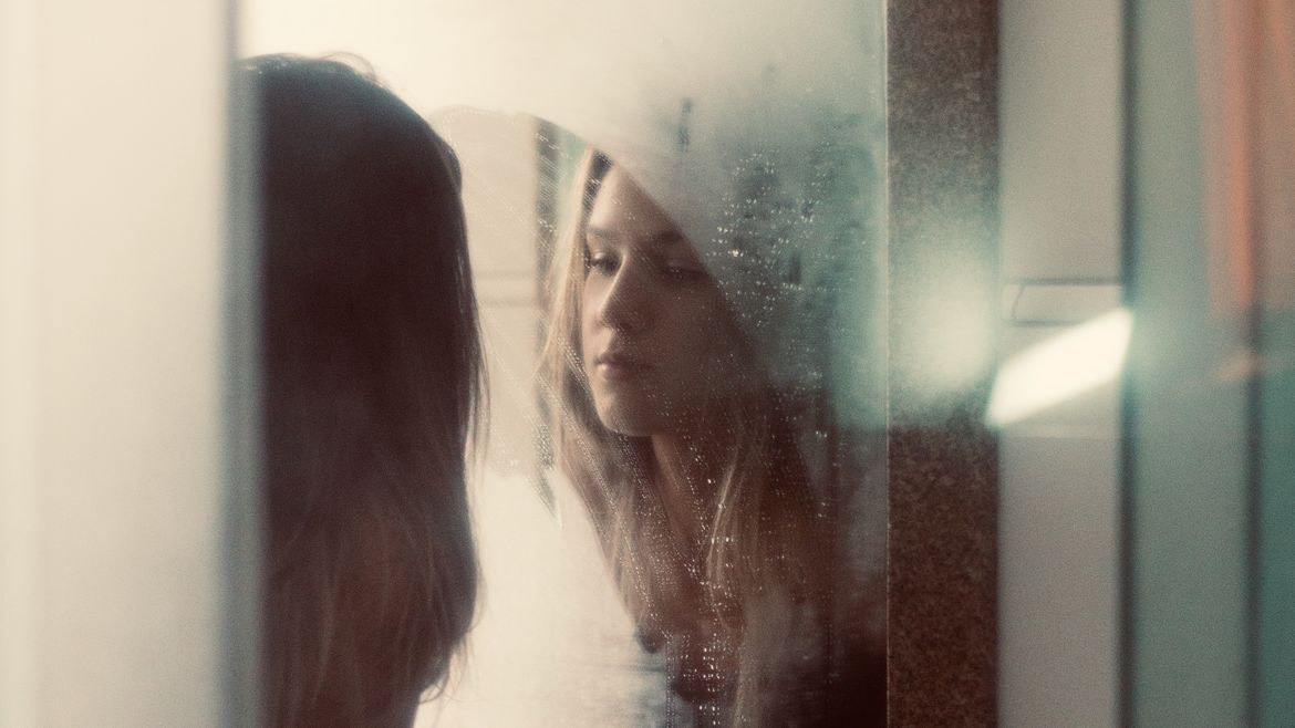 Cover Photo: image from the back of a young woman with long dark blond/light brown hair looking in a bathroom mirror, the top part of her head obscured