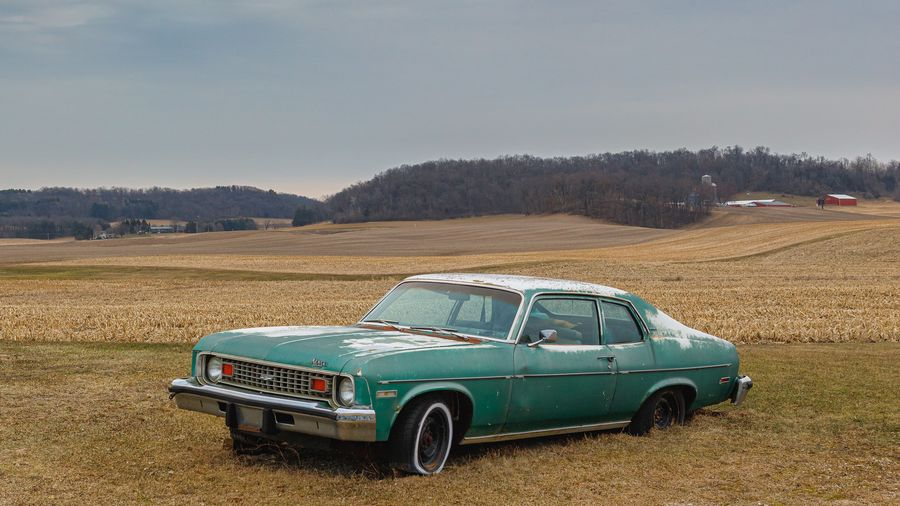 Cover Photo: This photograph shows an old green car sunk into brown grass off the side of a road. The sky is gray and it looks chilly, like an early spring day.