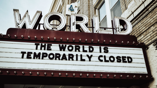 """Cover Photo: A photograph of an old theater marquee with capital letters spelling """"WORLD"""" above the sign. On the sign are block letters that read """"the world is temporarily closed."""""""