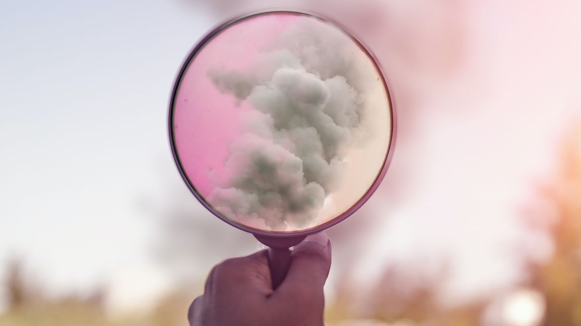 Cover Photo: This picture shows someone holding up to a magnifying glass filled with smoke. The smoke becomes pink and magical looking through the magnifying glass.