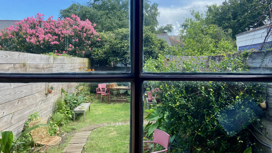 Cover Photo: view through an office window out into a wooden-fenced backyard filled with bushes, flowers and flowering trees, a table and red chairs, and a wooden bench