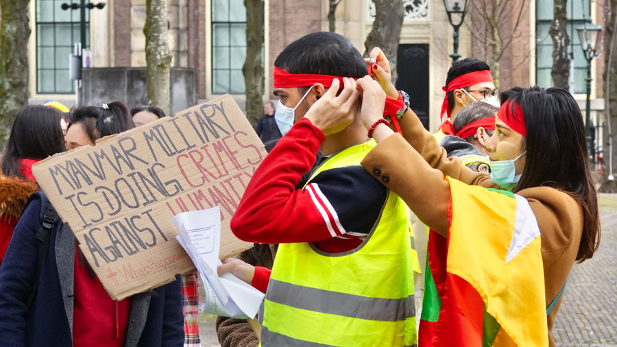 """Cover Photo: A photograph of protestors. A woman is tying a red bandanna around a man's head, while he holds a sign that says in all capitals: """" Myanmar military is doing crimes against humanity."""""""