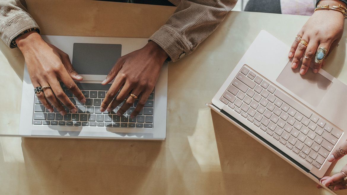 Cover Photo: This image shows two people sitting next to each other and typing on laptops. It's a close up of their hands and wrists and the vibe is pastel and pleasant.