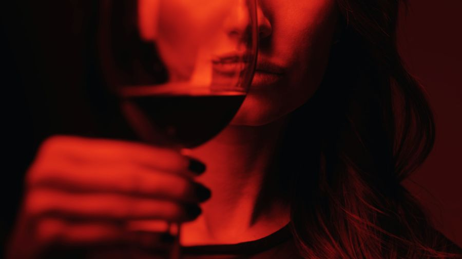 Cover Photo: This photograph shows a woman holding up a glass of red wine in front of her face. The photograph is very dark, with red light on the woman's face, so as to give the photo a dark, mysterious, sort of apprehensive tone.