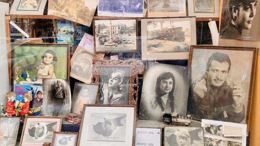 Cover Photo: This photograph looks into the window of a cluttered antique store, showing many old photographs and posters, all slightly faded from the sun.