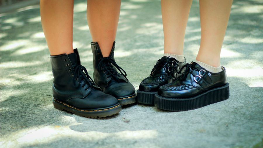 Cover Photo: This photograph shows two girls standing side by side, both wearing clunky Doc Martens. The sunlight behind their bare legs is dappled, like they are standing in the summer shade.