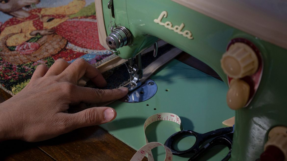 Cover Photo: This photograph shows a close up of a woman's hands sewing the edge of a piece of colorful fabric
