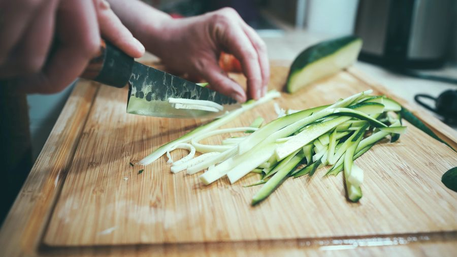 Cover Photo: This photograph shows a close up of someone thinly slicing a zucchini