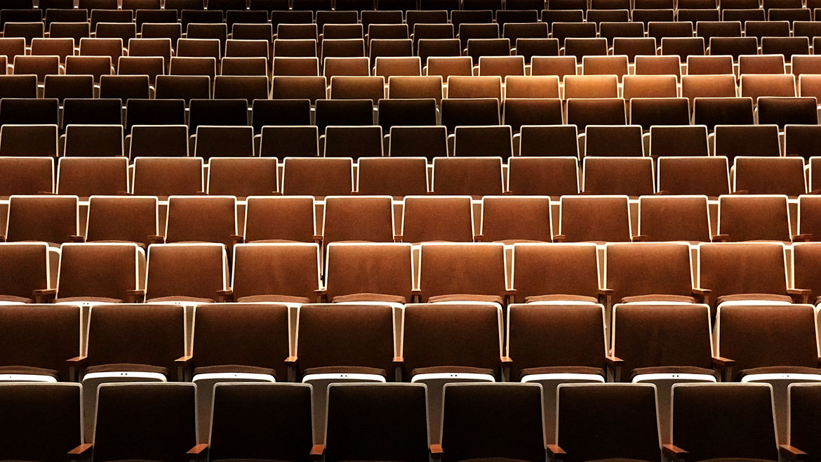 Cover Photo: A photograph of many rows of seats in an empty auditorium. All of the chairs are in shades of brown.