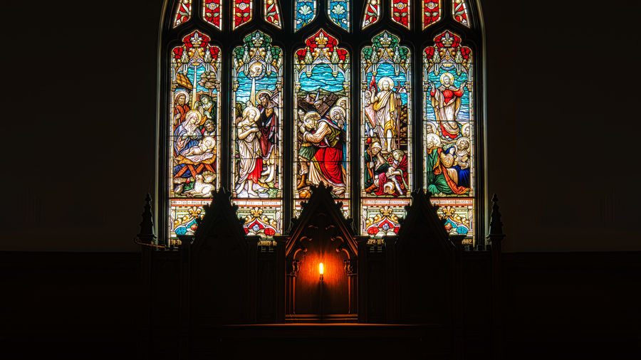 Cover Photo: A photograph of a five-panel stained glass window in a church.  In front of the window is an elaborate wooden platform with a single glowing light.