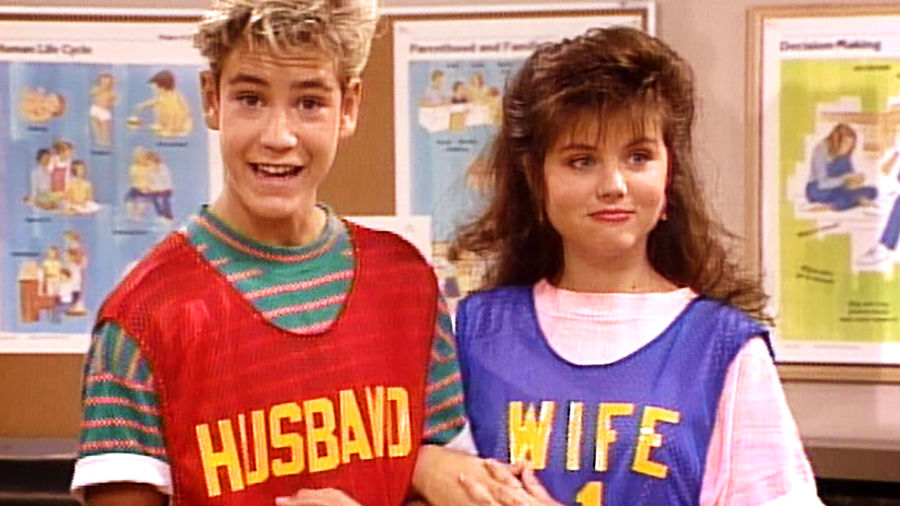 """Cover Photo: A screencap of the characters Zack Morris and Kelly Kapowski, a high school–aged blonde boy and brunette girl, holding hands and wearing matching jerseys that say """"husband"""" and """"wife."""" Zack's jersey is red and Kelly's is dark purple."""