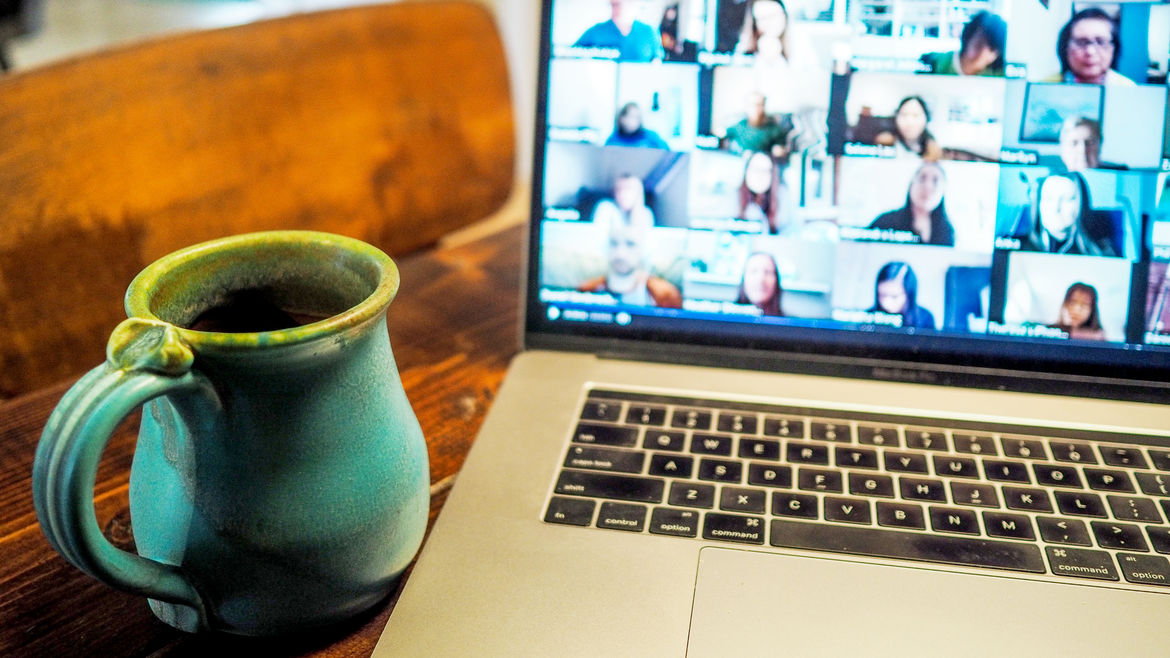 Cover Photo: This photograph shows a laptop open on a desk with a green mug sitting next to it. On the screen, we see blurry faces of people in a video chat meeting.