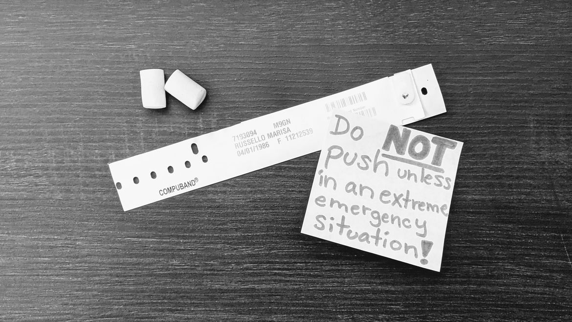 """Cover Photo: This black and white photograph shows a pair of foam earplugs and a plastic hospital bracelet sitting on a wooden surface next to a sticky note, which reads: """"Do NOT push unless in an extreme emergency situation!"""""""