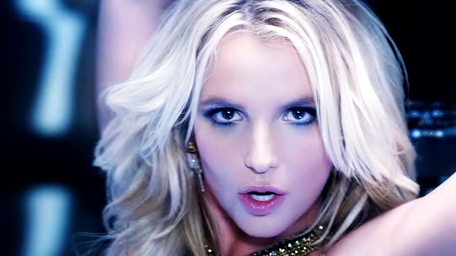 Cover Photo: A close-up photograph of Britney Spears, a white woman with platinum blonde hair, as she stares into camera and dances during a music video.