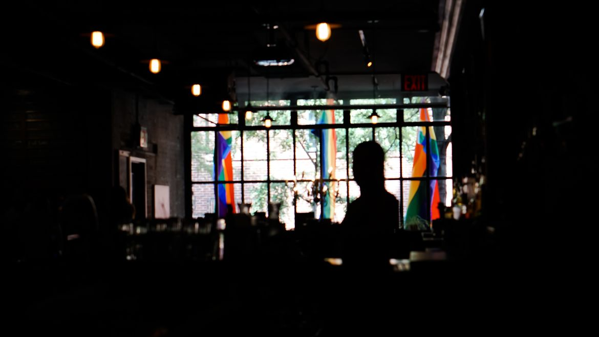 Cover Photo: This photograph was taken in a dark bar. The bar, tables, and one person are outlined in shadow, but at the front of the bar there are big windows that look out onto the street. Three pride flags hang outside just past the windows.
