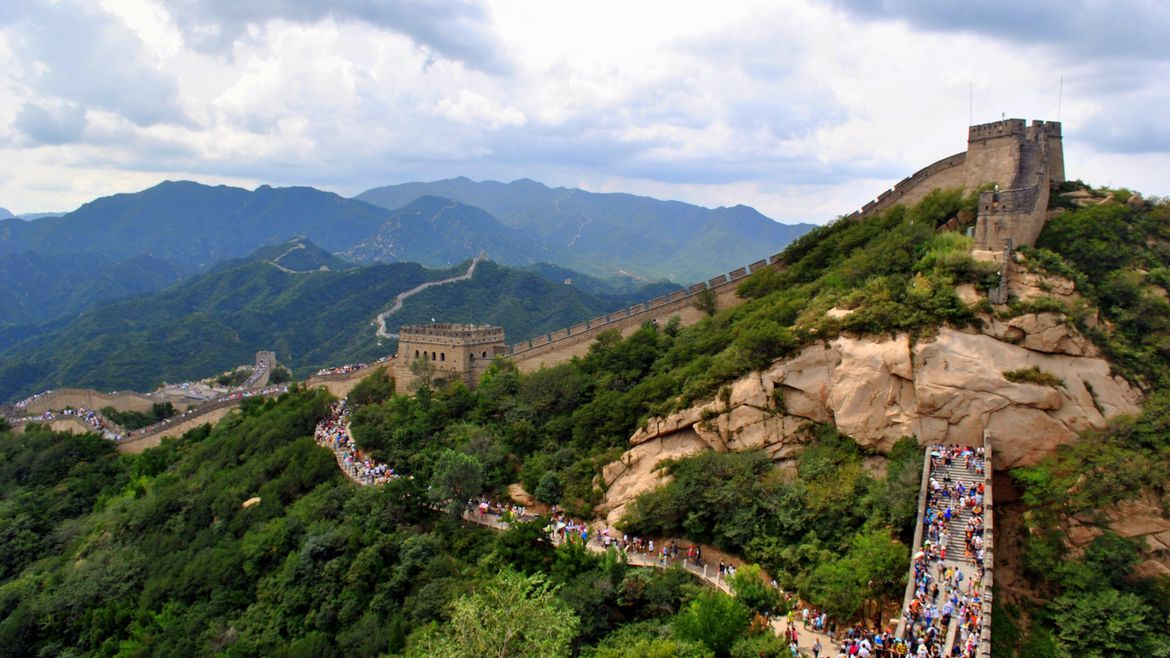 Cover Photo: This photograph shows the Great Wall of China, stretching over green mountains on a blue-sky, white-cloud filled day. There are many people walking on the wall, appearing as small colorful spots along the walkways.