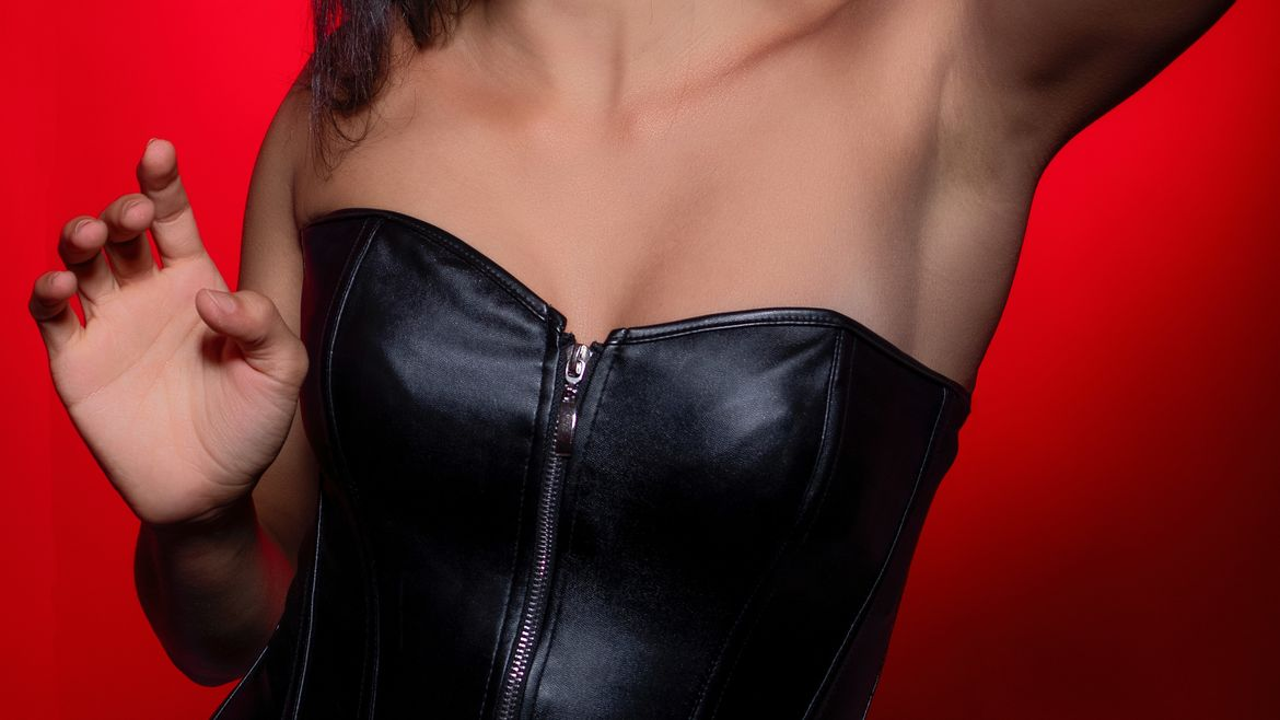 Cover Photo: This photograph shows a close up of a woman wearing a leather corset. her hands are raised, as if she is posing, and the background of the image is bright red.