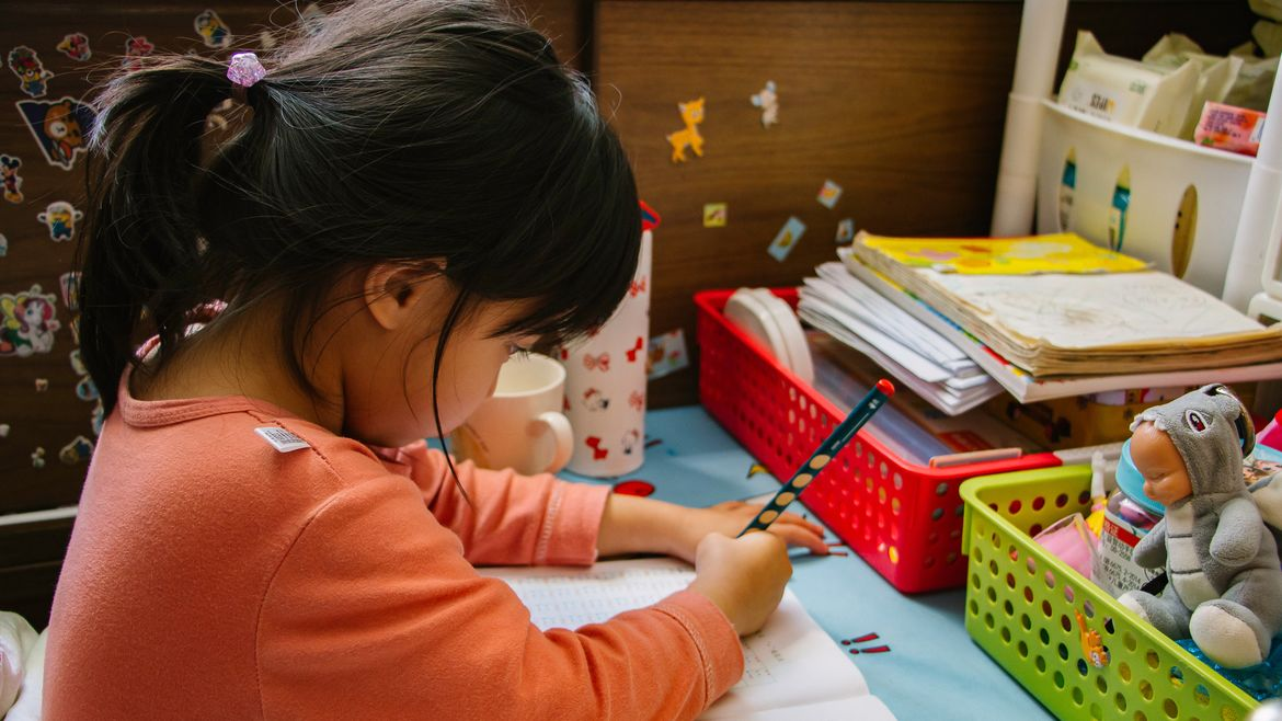Cover Photo: This photograph shows a young girl with dark hair focusing on writing in her journal. She's at a small, colorful desk, with stickers around her, like she is in a kindergarten classroom