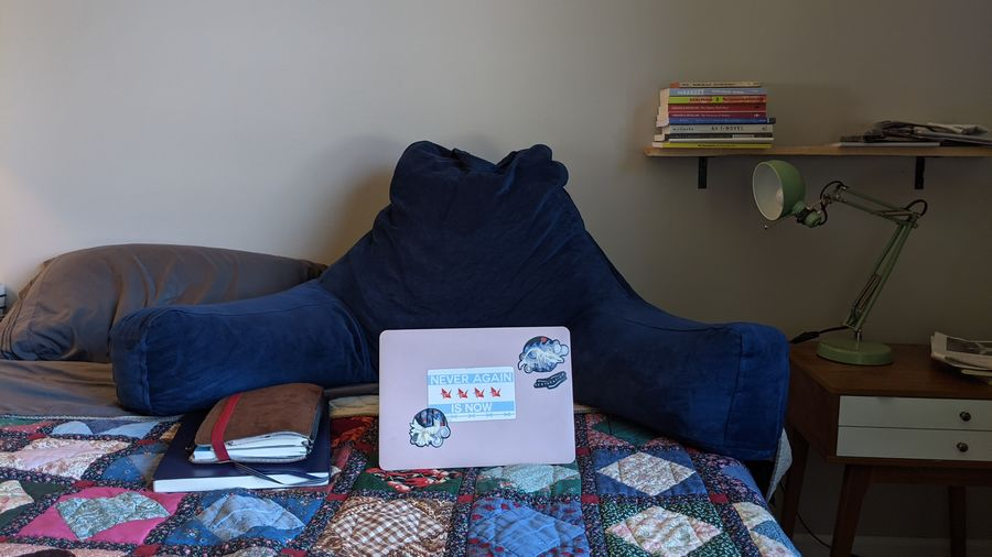 Cover Photo: This photograph shows the author's bedroom writing set up: a large pillow, with her laptop and notebooks sitting in front of it on the bed. To the right, we see a bookshelf and an adjustable lamp.