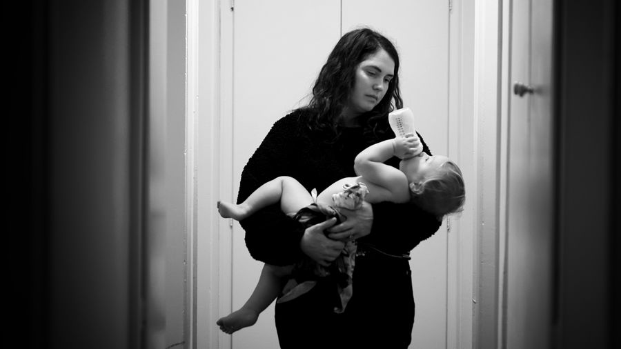 Cover Photo: An image of a woman holding a baby in a hallway