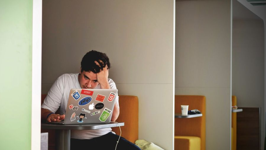 Cover Photo: This photograph shows a man sitting inside a study cubicle with his laptop. He looks frustrated; his hand is clutching his hair and he is staring at his computer with intensity.