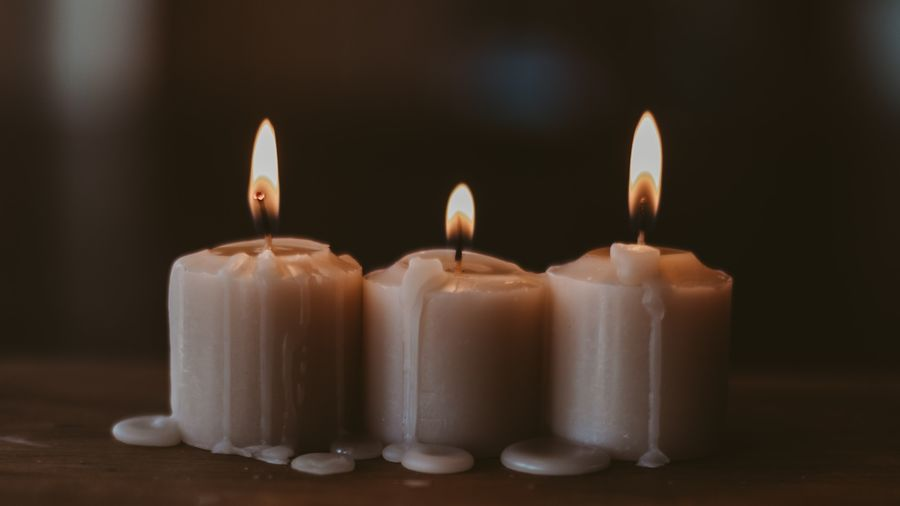 Cover Photo: This image is a close up of three short candles. Their wax has dripped onto the wooden table where they sit and the background is blurry and warm-looking.