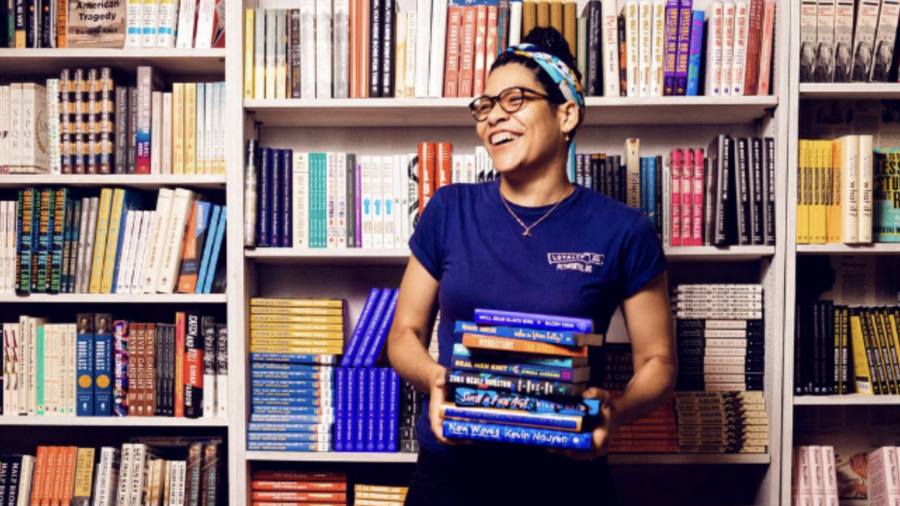 Cover Photo: A photograph of Hannah Oliver Depp,  a black woman in a dark blue t-shirt and glasses, holding a colorful stack of books and standing in front of full wall-to-wall bookshelves. She looks toward the left of the frame and smiles.