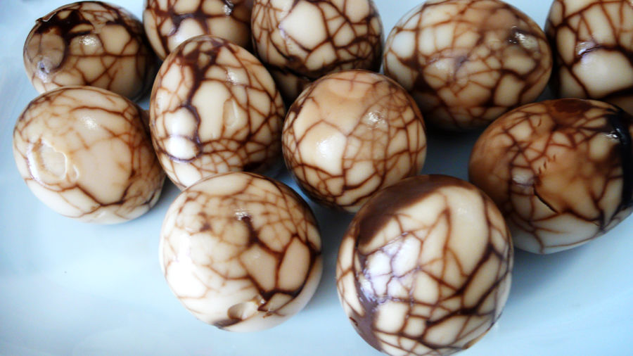 Cover Photo: A photograph of a dozen tea eggs, unpeeled and on a flat surface. The eggs are a sepia brown with a network of dark brown crack-like lines across their surface.