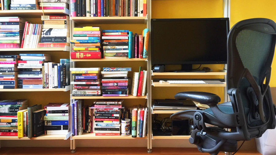 Cover Photo: Photograph of bookshelves with a desk integrated into the shelving system, featuring a monitor and other computer paraphernalia
