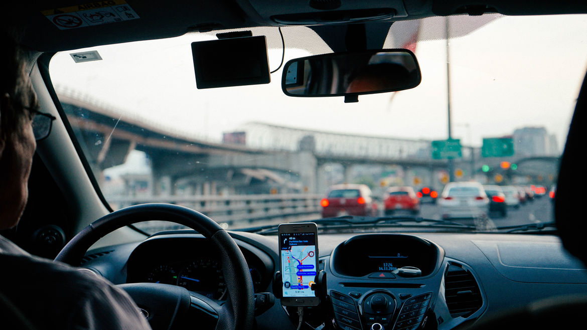 Cover Photo: A perspective shot from the back of a car in an Uber