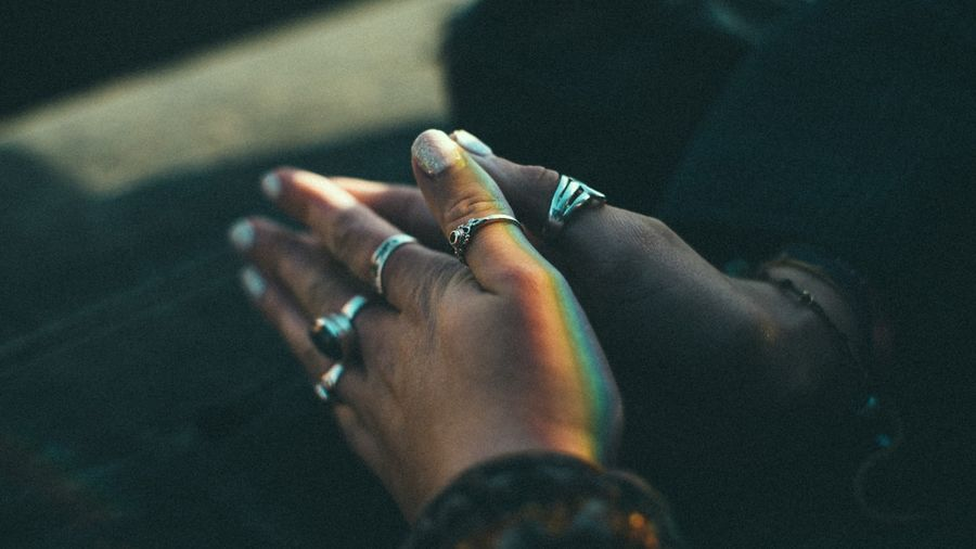 Cover Photo: This photograph shows a pair of hands clasped in casual prayer. The fingernails are painted with sparkly polish and the hands wear several rings. A rainbow, as if cast from a prism, shines across the thumb of one hand.