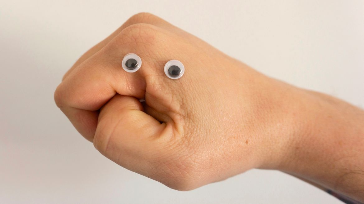 """Cover Photo: This image is a photograph of a hand, turned sidewise so it looks like the thumb meeting the fingers is a face. There are googly eyes stuck to the hand above its """"mouth."""""""
