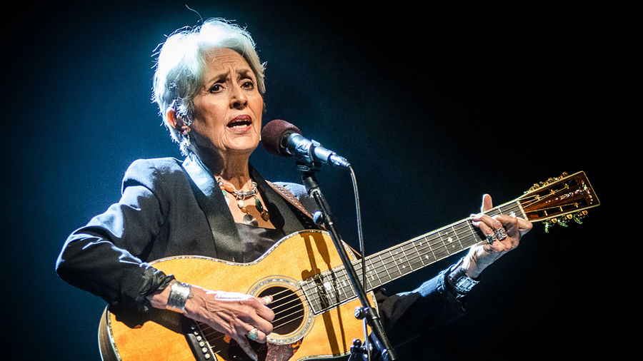 Cover Photo: This photograph is of singer/songwriter Joan Baez, performing on stage while singing into a microphone and strumming her guitar. She looks serious and a spotlight accentuates her shining gray hair.