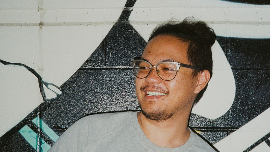 Cover Photo: Adrian De Leon, light brown skinned with freckles and silver framed glasses, in a grey crew neck sweatshirt. He's standing in front of a white brick wall with black airbrushed spots.