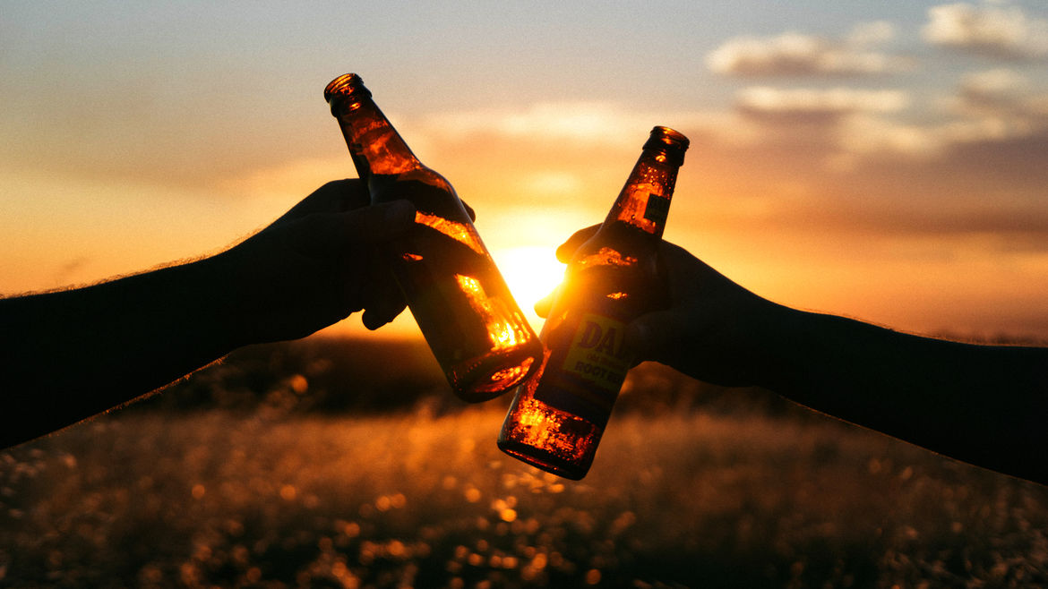 Cover Photo: A photograph of two hands clinking together beer bottles in front of a sunset.