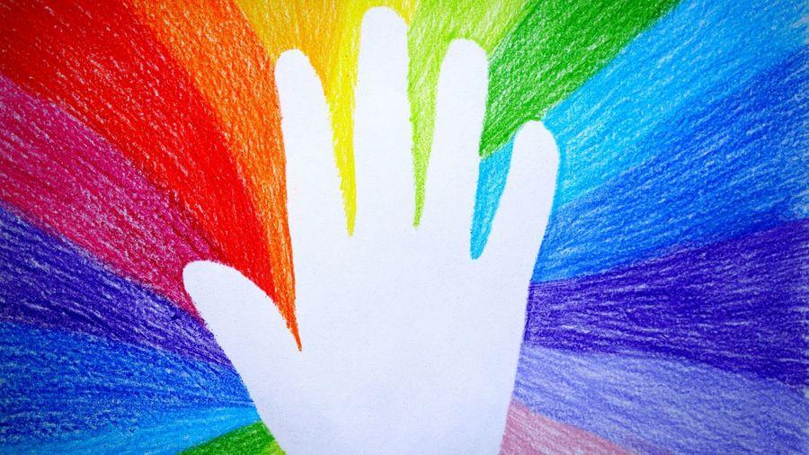 Cover Photo: A hand against  a hand drawn  rainbow