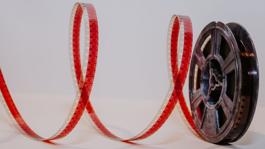 Cover Photo: This photograph shows an old film reel spooled out against a white background.