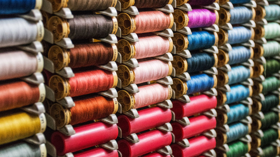 Cover Photo: Several rows of multi-colored sewing threads arranged on  a rack. The colors span the rainbow spectrum.
