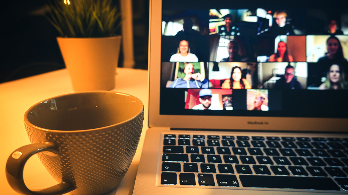 Cover Photo: An image of a computer screen with people on the screen and a coffee cup beside it