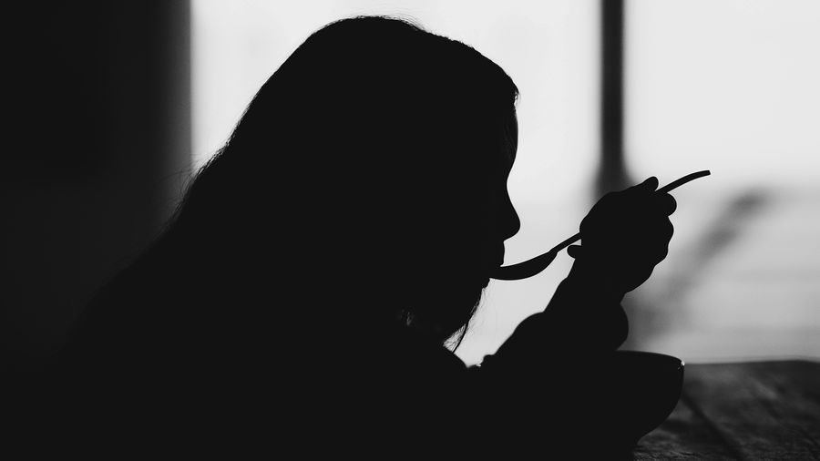Cover Photo: A black and white photograph of a young girl silhouetted against a window. She is holding a spoon to her mouth and eating from a bowl.