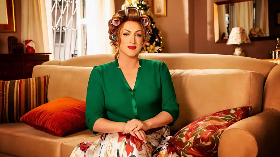 Cover Photo: Paulo Gustavo as the character of Dona Herminia seated on a couch in a green blouse and white floral skirt
