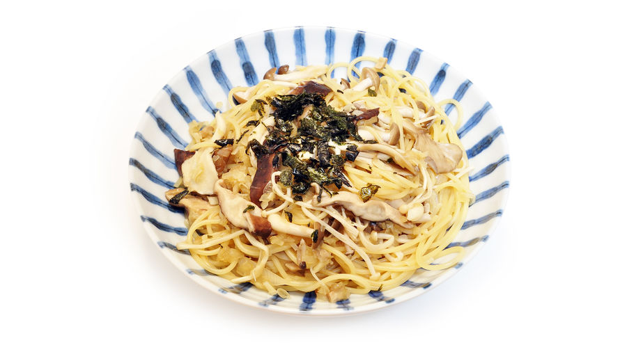 Cover Photo: a heap of spaghetti  noodles tossed with mushrooms, garlic, and topped with what appears to be shredded seaweed, resting in a shallow blue and white striped bowl