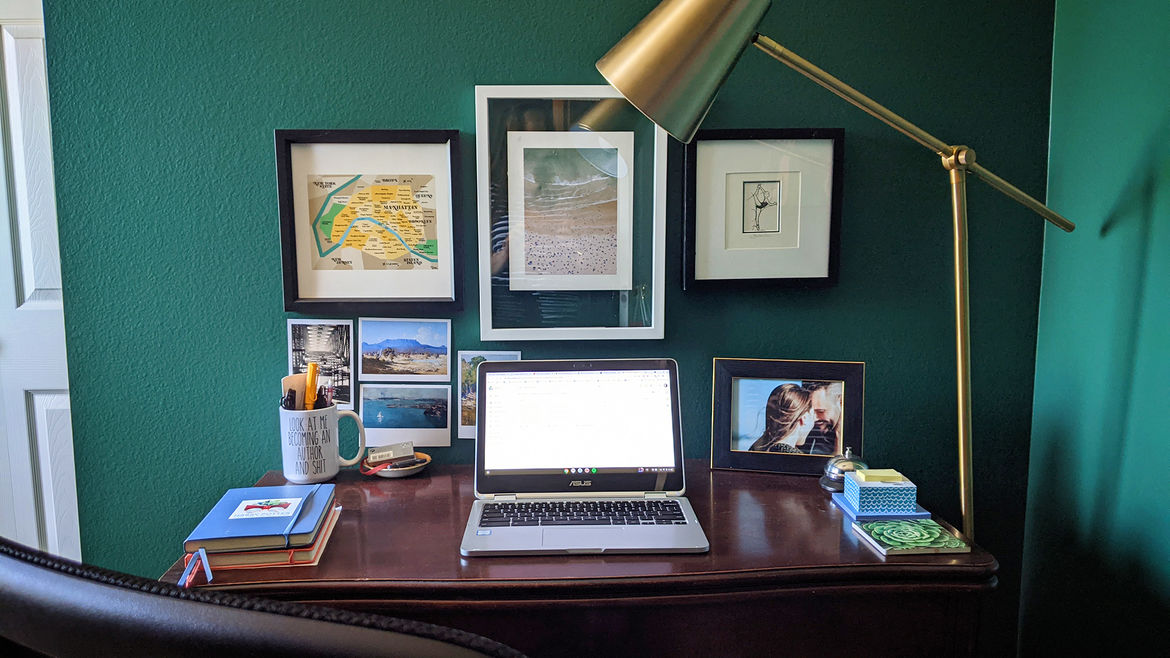 Cover Photo: A desk with a laptop, a lamp, framed photographs, and a bell much like one found at hotel front desks