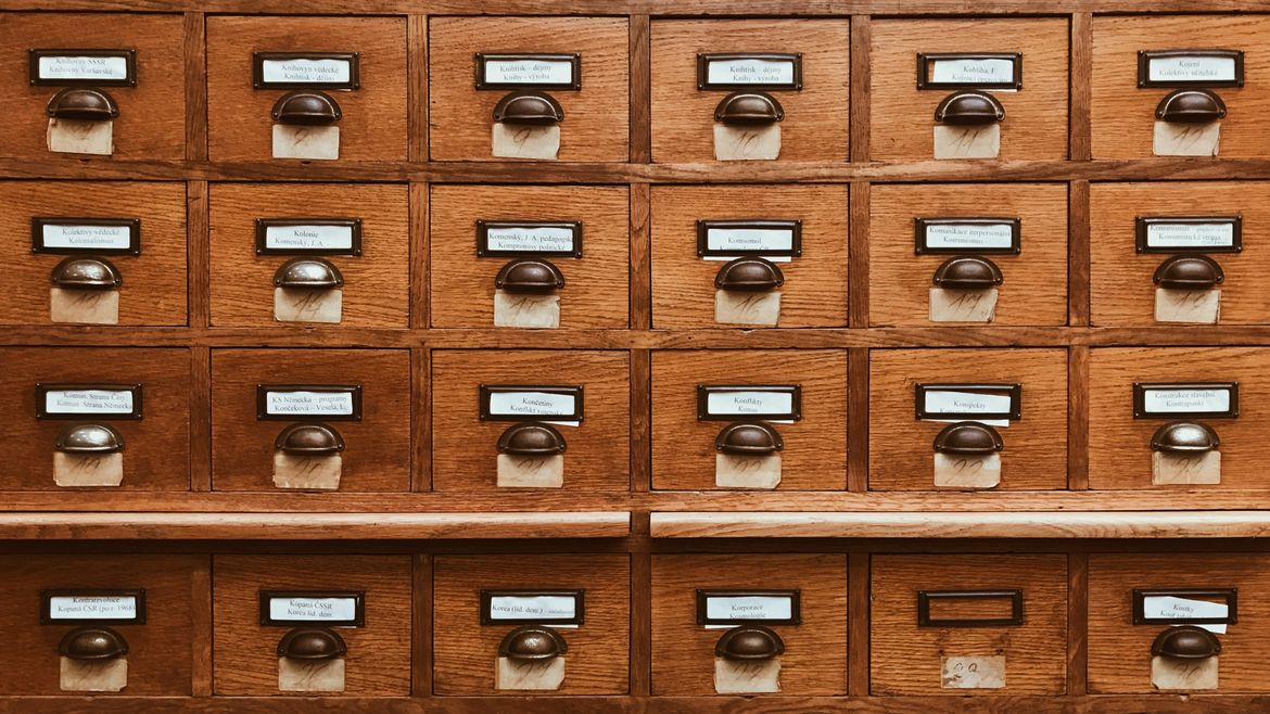 Cover Photo: A photograph of several rows of brown wooden drawers with small labels on each one, as if in a library database.